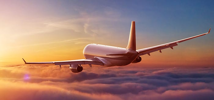 commercial airplane flying above clouds in sunset light